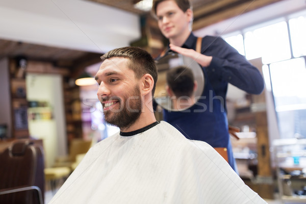 man and hairdresser with mirror at barbershop Stock photo © dolgachov