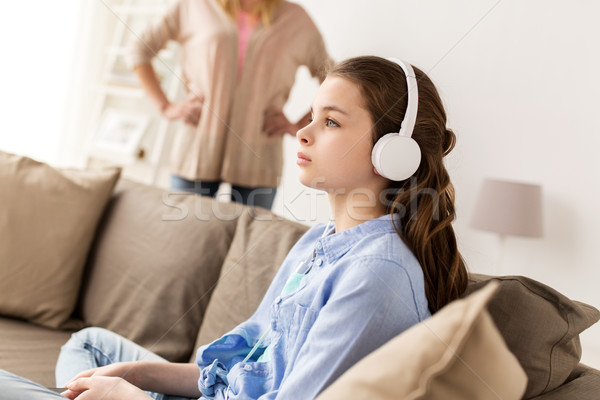 girl with earphones and angry mother at home Stock photo © dolgachov