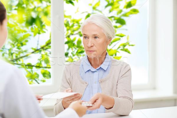 doctor giving prescription and drug to woman Stock photo © dolgachov