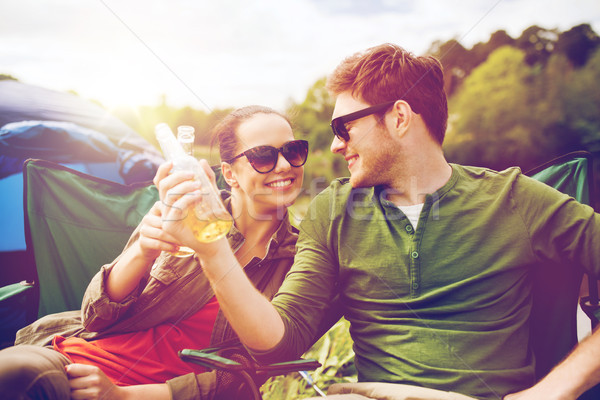 happy couple clinking drinks at campsite tent Stock photo © dolgachov