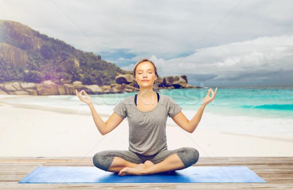 woman doing yoga meditation in lotus pose on beach Stock photo © dolgachov