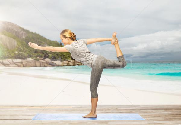 woman doing yoga lord of the dance pose on beach Stock photo © dolgachov