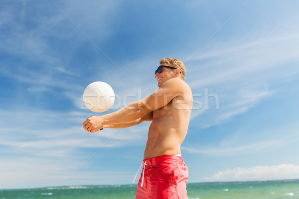 young man with ball playing volleyball on beach Stock photo © dolgachov