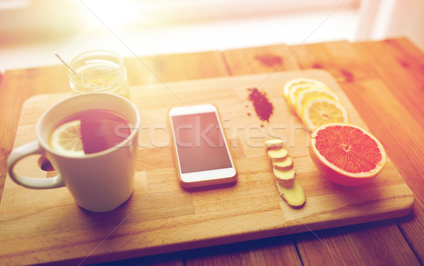 smartphone with cup of lemon tea, honey and ginger Stock photo © dolgachov