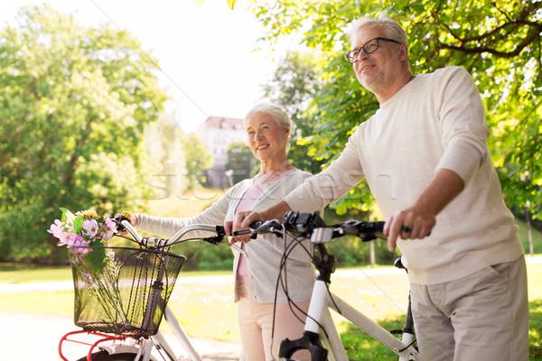 happy senior couple with bicycles at summer park Stock photo © dolgachov