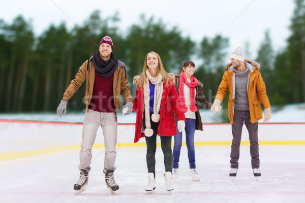 friends holding hands on outdoor skating rink Stock photo © dolgachov