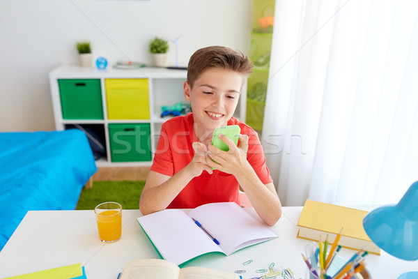 student boy with smartphone distracting from study Stock photo © dolgachov