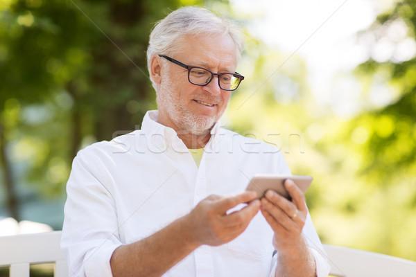 senior man with smartphone at summer park Stock photo © dolgachov