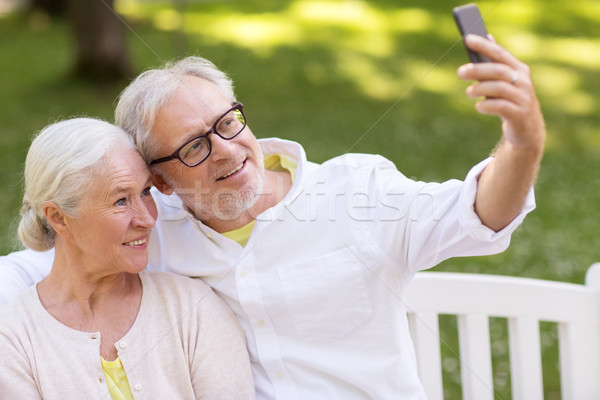 senior couple taking selfie by smartphone at park Stock photo © dolgachov