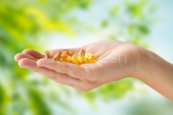 hand holding cod liver oil capsules Stock photo © dolgachov