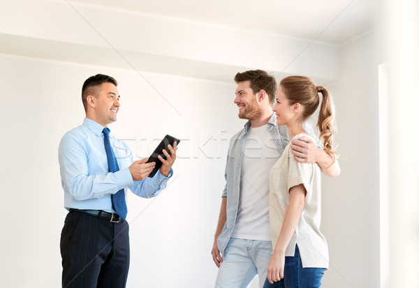 couple and realtor with tablet pc at new home Stock photo © dolgachov