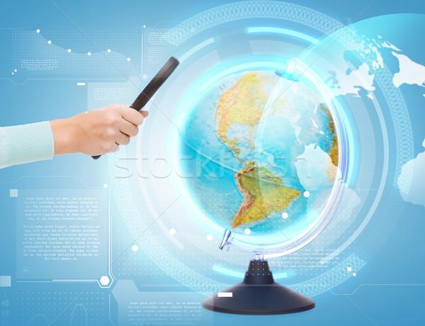 woman hand holding magnifying glass over globe Stock photo © dolgachov