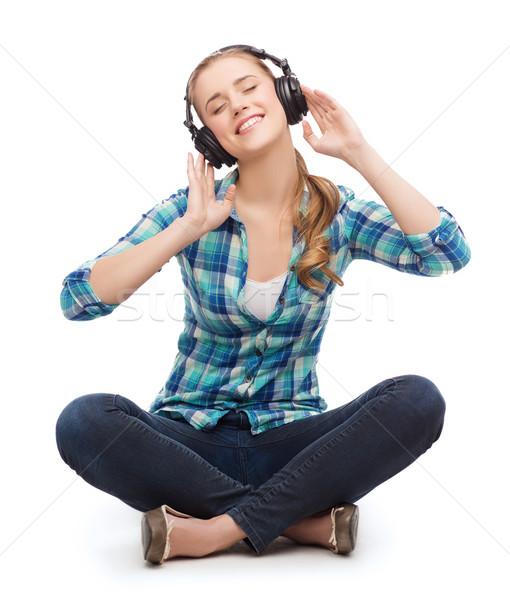 Młoda kobieta muzyki słuchawki technologii uśmiechnięty posiedzenia Zdjęcia stock © dolgachov