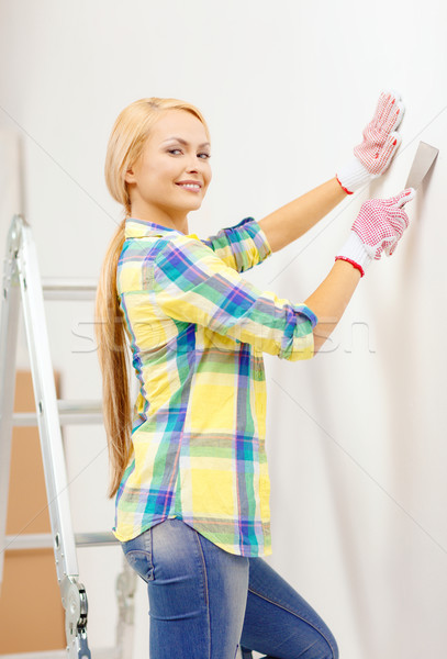 smiling woman in gloves doing renovations at home Stock photo © dolgachov