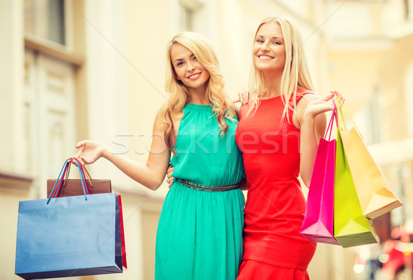two beautiful women with shopping bags in the ctiy Stock photo © dolgachov
