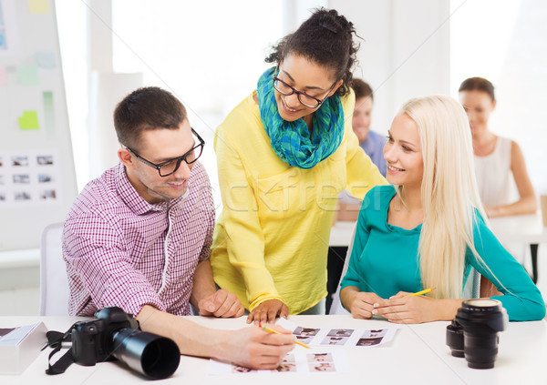 smiling team with printed photos working in office Stock photo © dolgachov