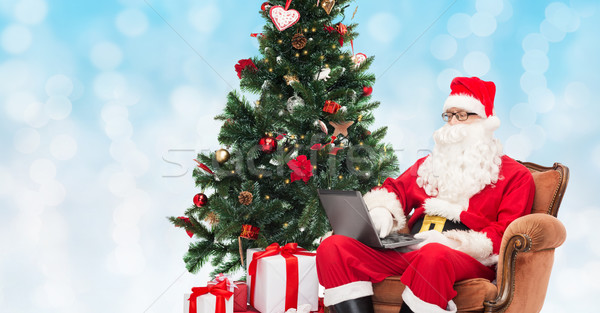 man in costume of santa claus with laptop Stock photo © dolgachov