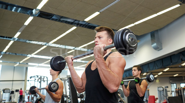 group of men flexing muscles with barbell in gym Stock photo © dolgachov