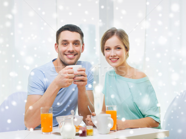 Stock photo: smiling couple having breakfast at home