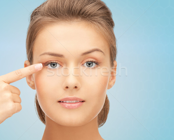 beautiful young woman pointing finger to her eye Stock photo © dolgachov