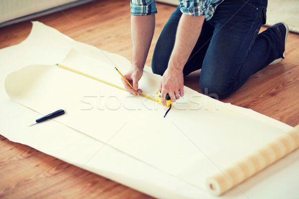 Stock photo: close up of male hands measuring wallpaper