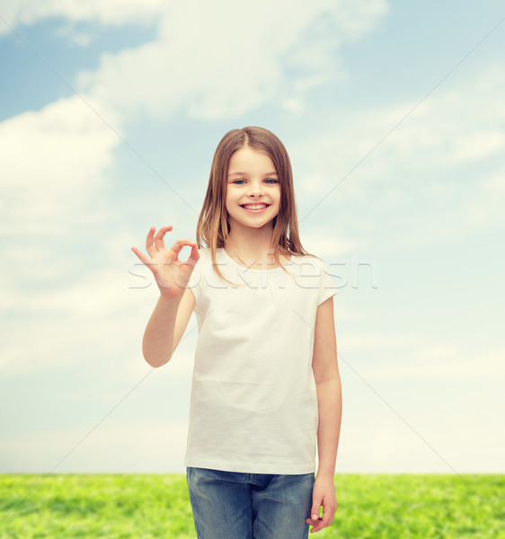 little girl in white t-shirt showing ok gesture Stock photo © dolgachov