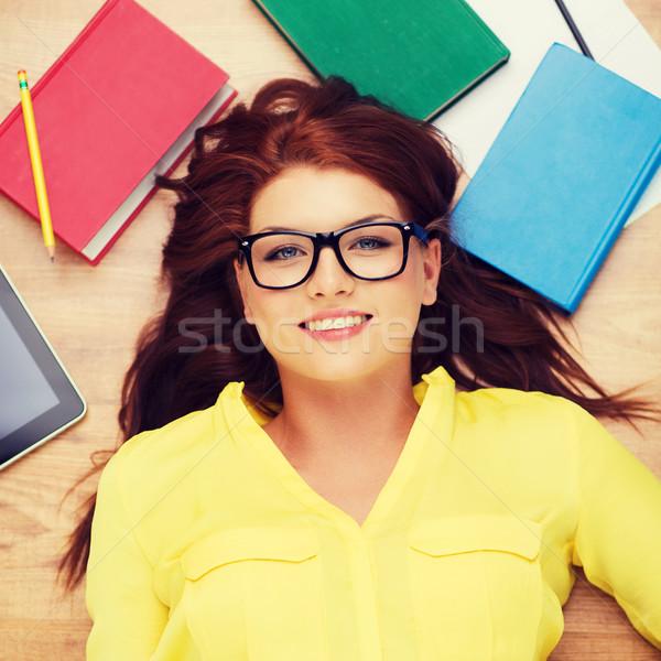 smiling student in eyeglasses lying on floor Stock photo © dolgachov