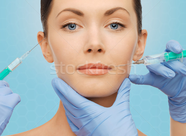 woman face and surgeon hands with syringes Stock photo © dolgachov