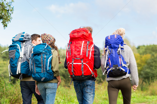group of friends with backpacks hiking Stock photo © dolgachov