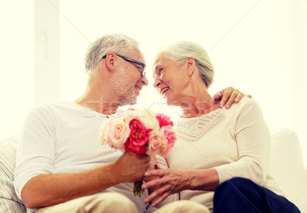 Stock photo: happy senior couple with bunch of flowers at home