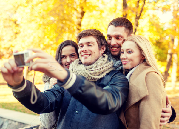 Stock photo: group of smiling men and women making selfie