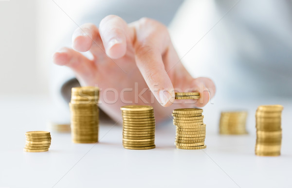 close up of female hand putting coins into columns Stock photo © dolgachov