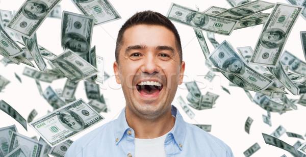 laughing man with falling dollar money Stock photo © dolgachov