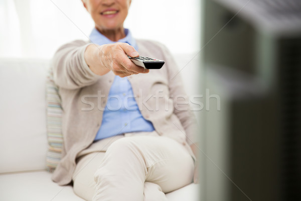 close up of happy senior woman watching tv at home Stock photo © dolgachov