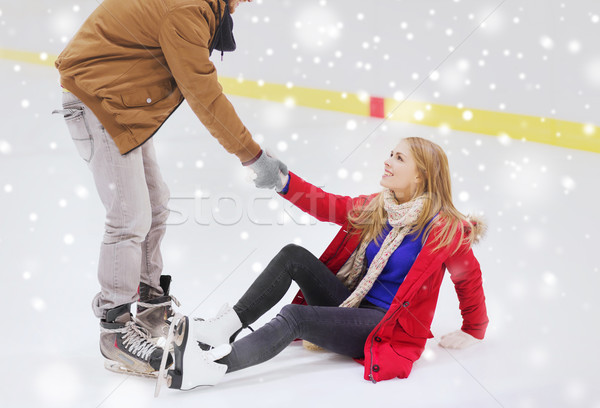 Stock photo: man helping women to rise up on skating rink