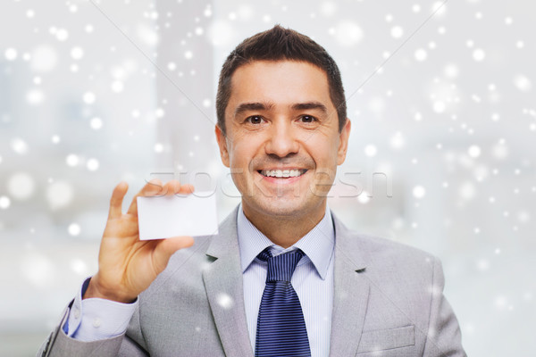 smiling businessman in suit showing visiting card Stock photo © dolgachov