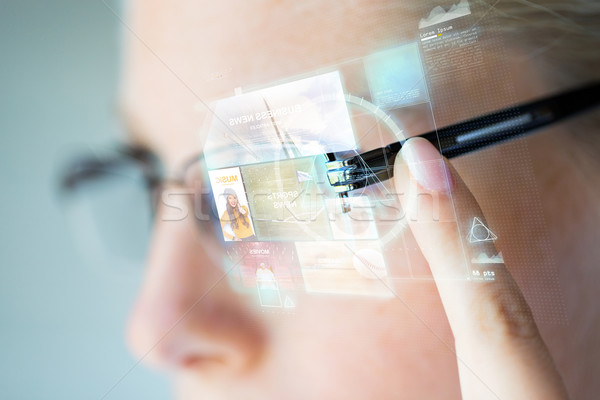 close up of woman in glasses with virtual screen Stock photo © dolgachov