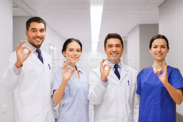 group of medics at hospital showing ok hand sign Stock photo © dolgachov