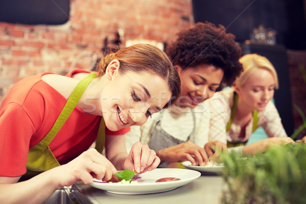 happy women cooking and decorating dishes Stock photo © dolgachov