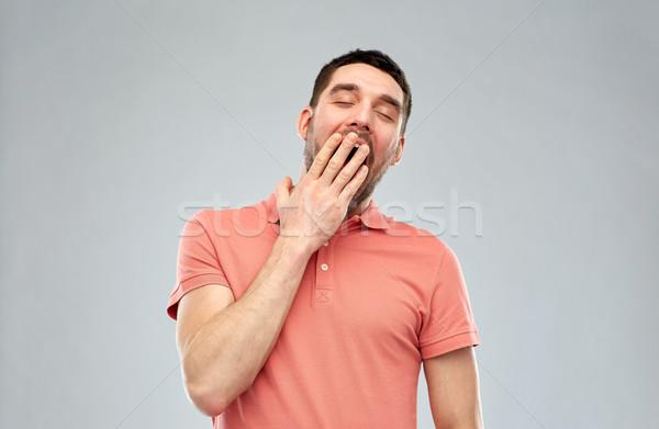 yawning man over gray background Stock photo © dolgachov