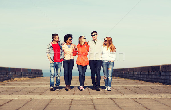 happy teenage friends walking along city street Stock photo © dolgachov