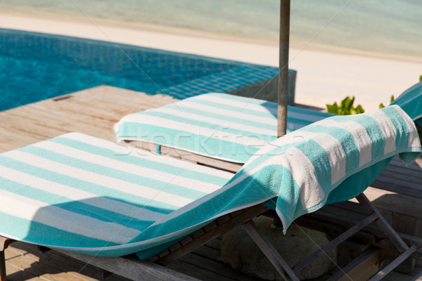 parasol and sunbeds by sea on maldives beach Stock photo © dolgachov