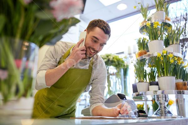 Férfi okostelefon készít jegyzetek virágüzlet emberek Stock fotó © dolgachov