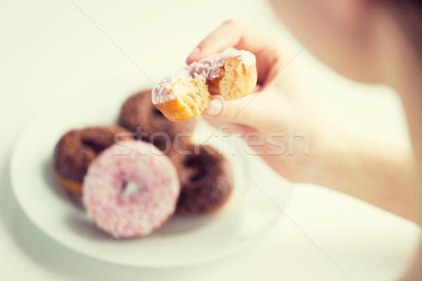 close up of hand holding bitten glazed donut Stock photo © dolgachov
