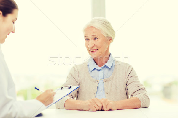 doctor with clipboard and senior woman at hospital Stock photo © dolgachov