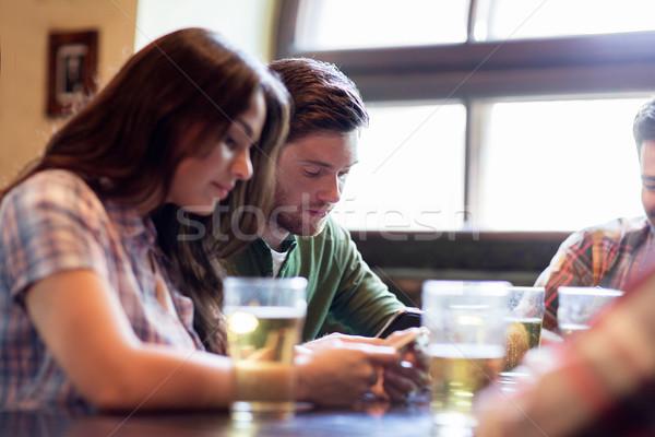 Vrienden smartphones drinken bier pub mensen Stockfoto © dolgachov