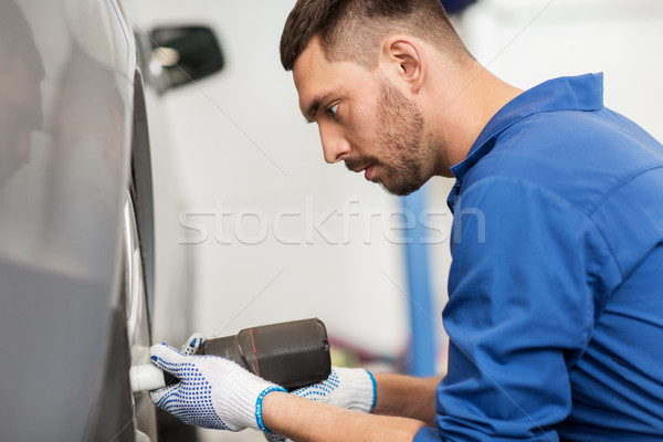 mechanic with screwdriver changing car tire Stock photo © dolgachov