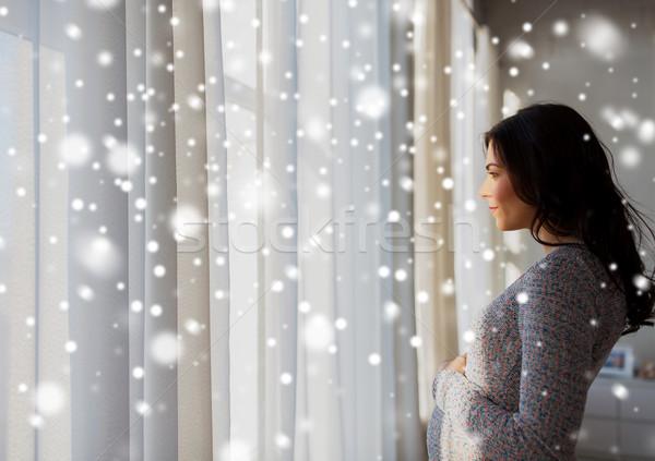 Felice donna incinta guardando finestra gravidanza Foto d'archivio © dolgachov