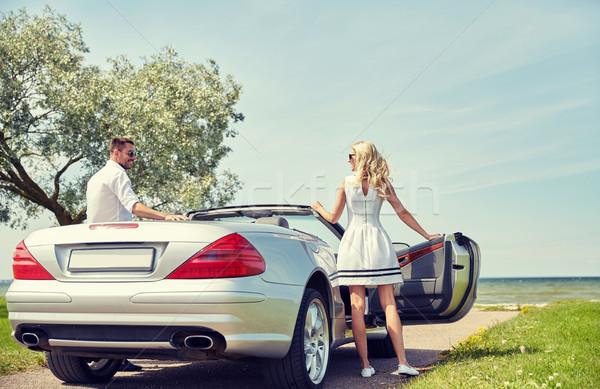 happy man and woman near cabriolet car at sea Stock photo © dolgachov