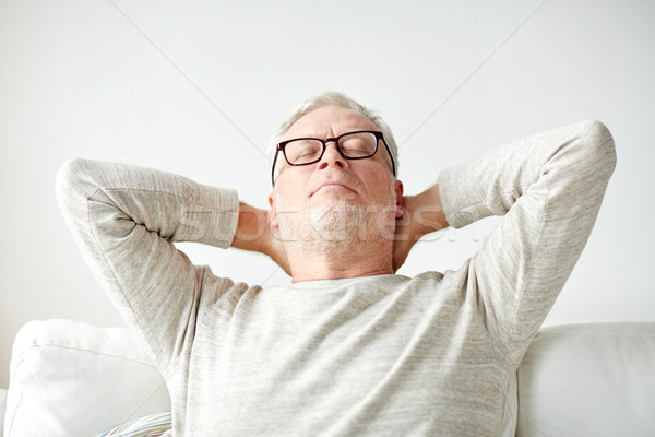 senior man in glasses relaxing on sofa Stock photo © dolgachov